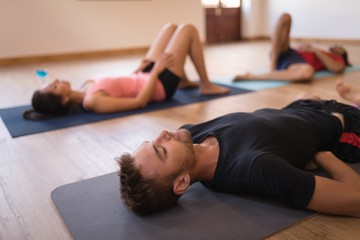 Young people practicing yoga exercise in the gym