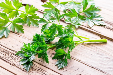 Parsley herb on the wooden background.