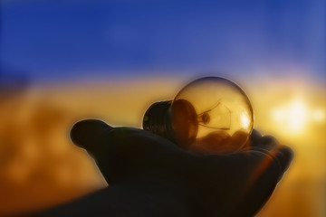 the light bulb lies on the palm of your hand , sunset