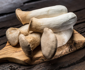King oyster mushrooms on the wooden background.