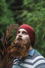 Bearded man standing at branch in forest