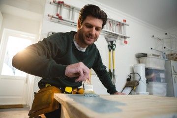 Male carpenter painting a table