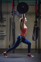 Sporty woman training with barbell