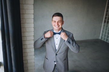 A beautiful and stylish bridegroom in an interesting studio fights for a bow tie and smiles.