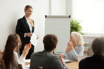 Executive business team congratulating successful female manager with applause at conference meeting, corporate group clapping hands appreciating leader for good result, gratitude ovation concept