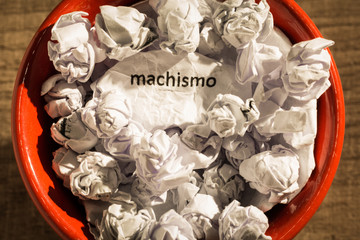 Crumpled paper written machismo, portuguese and spanish word for chauvism, inside the trash can. Paper balls. Concept of old and abandoned idea or practice.