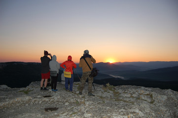 tourists watch the sun rise on the mountain