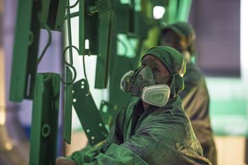 Workers wearing protective masks spraying metal
