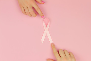 Women's hands with pink tape as symbol of women illness mammary cancer isolated on pink background