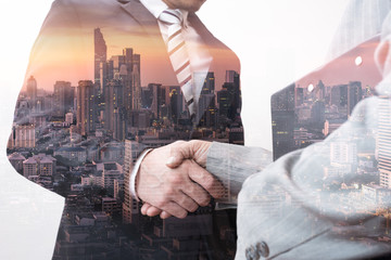 The double exposure image of the businessman handshaking with another one during sunrise overlay with cityscape image. The concept of modern life, business, city life and partnership.