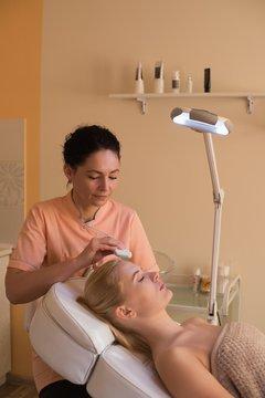 Beautician using ultrasonic scrubber on female customer
