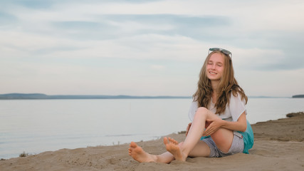 One beautiful teenage girl with brown hair outside on a beautiful summer day. A girl is doing herself a foot massage. Rubbing cream from sunburn. Sunburns are visible on the feet.