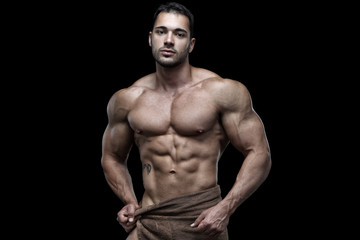 Sexy muscular male posing in front of black background