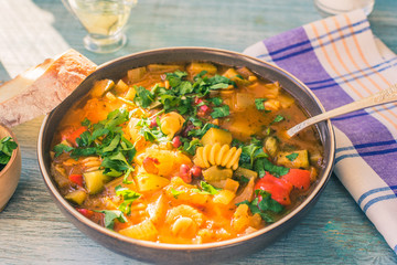 Rustic Italian minestrone soup with pasta and chopped green parsley in a plate on a painted wooden table close-up with a napkin - top view