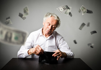 Old man in white and empty wallet. Accounting, taxes and poverty concept. Falling dollars.