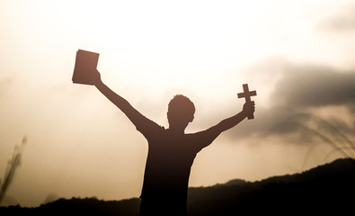 Human holding Bible book and christian cross with light sunset background