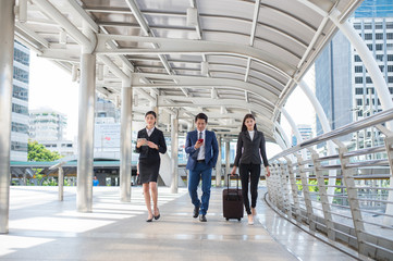 businessman and businesswoman walk together with mobile,  tablet and luggage on the public street, business travel