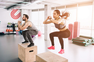 A picture of slim and well-built young man and woman doing jumps on platform. It is a hard exercise but they are doing it successful and with dilligence.