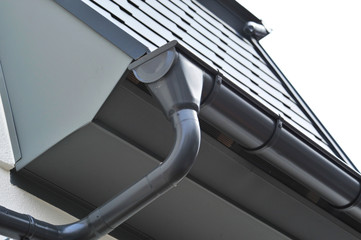 Dachrinne aus beschichtetem Metall . Dach mit beschichteten Aluminiumschindeln gedeckt