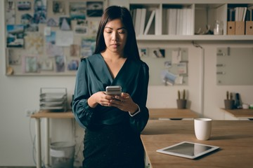 Executive using mobile phone in office