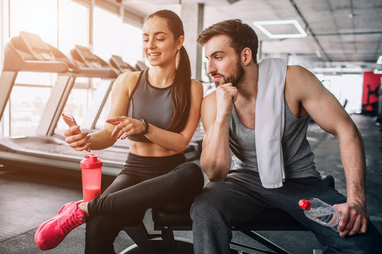 Attractive and nice people sitting on the sport bench and relaxing after long-term exercising. Girl shows something on the phone to her partner.