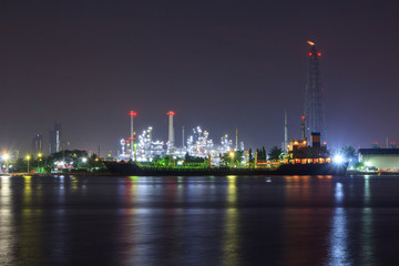 Oil refinery at the river in sunrise time / Big Factory in night time