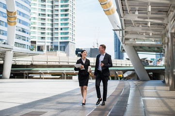 Asian business woman wear suit holding document file on hand and walking together with  Caucasian businessman in the city and talk about business future.