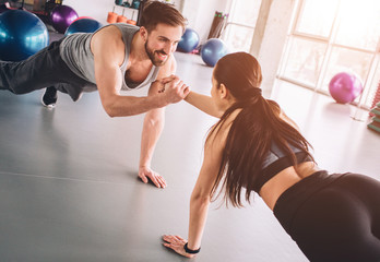 Two people that love fitness are standing on one hand in plank position and holding each other with another hand with a smile. It's nice and adorable scene.