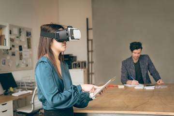 Female executive using virtual reality headset and digital