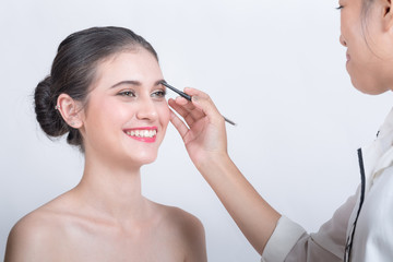 Young beautiful woman applying make-up by make-up artist isolated on white.