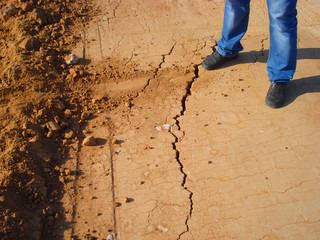 The man standing on cracked soil