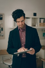Executive using digital tablet in office
