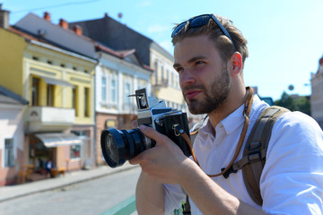 Tourist takes picture of cityscape. Man with beard