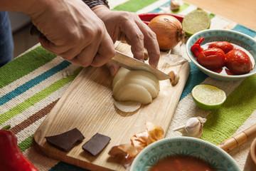 Men's hands cutting onion on chopping board
