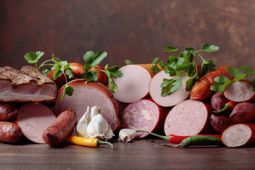 Different sausages and smoked meats on a  wooden table .