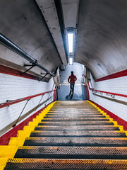 Young man in the red jacket rushing down the stairs of the Tube underpass. White ceramic wall tiles and metal staircase with red handrail at Chalk Farm Underground Station.
