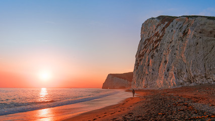 Sunset at Durdle Door beach. Lone fisherman walks toward the white cliffs, colored red by the setting sun. People are standing on the top of a cliff at Jurassic Coast near Lulworth in Dorset, England.