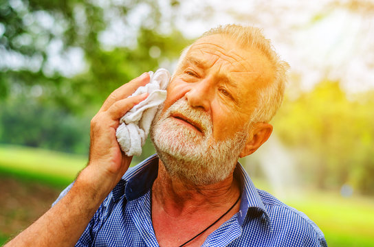 Senior man wiping sweat of his  with towel in park