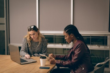 Female executives using laptop and digital tablet