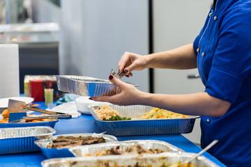 cook in a blue uniform puts a salad in a tray closeup