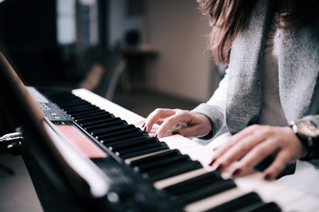 Close-up image of unrecognizable female person playing piano.