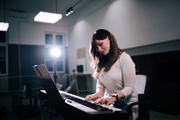 Beautiful female composer playing piano.