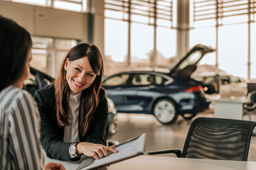 Smiling car saleswoman discussing  a contract with a female customer.