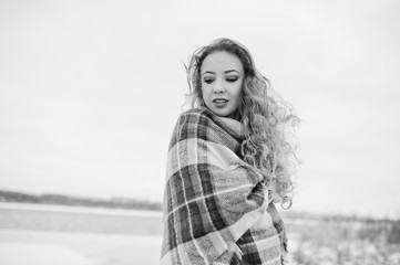 Curly blonde girl in checkered plaid against frozen lake at winter day.