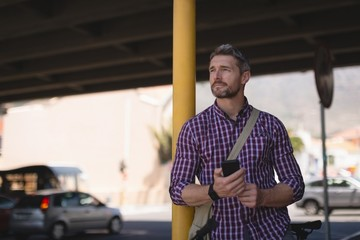 Man holding mobile phone while leaning on pole