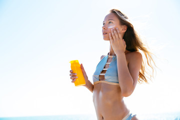 Charming woman in stylish swimsuit putting tanning cream on her face, sunbathing on the beach. Healthcare.
