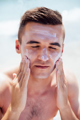 Young man putting tanning cream on his face, sunbathing on the beach. Healthcare.