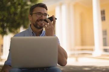 Man talking on mobile phone while using laptop
