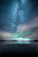 Tuinposter Noorderlicht Northern Lights aka Aurora Borealis behind fast moving clouds with reflections on lake