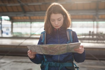 Traveler with backpack looking at map while waiting for train